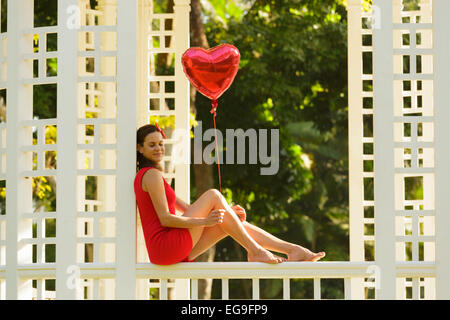Woman with red heart shape balloon sitting on park bench - Stock Photo