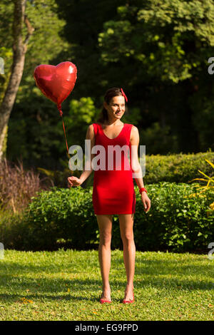 Woman with red heart shape balloon standing in park - Stock Photo