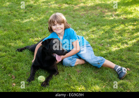 Boy (6-7) lying on lawn with dog - Stock Photo