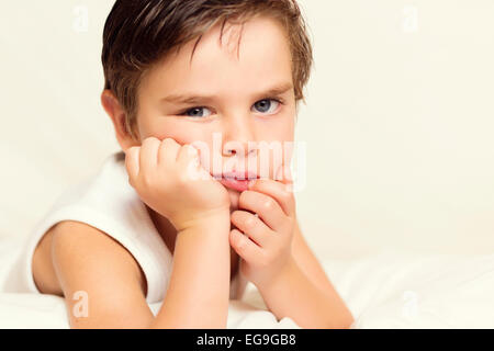 Portrait of boy with hand on chin - Stock Photo