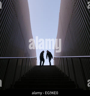 Symmetrical image of two silhouette people on top of stairs, walls on sides - Stock Photo