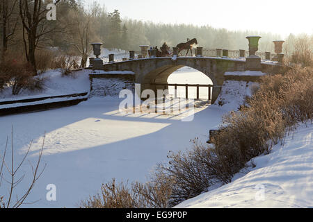 winter sunny landscape with horse-drawn carriage on old bridge - Stock Photo