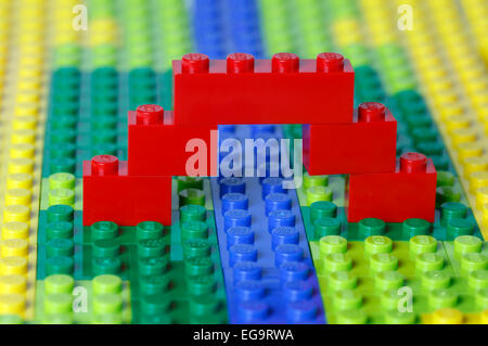 A red bridge over a blue stream in a green and yellow open landscape model all made of interlocking Lego bricks. - Stock Photo