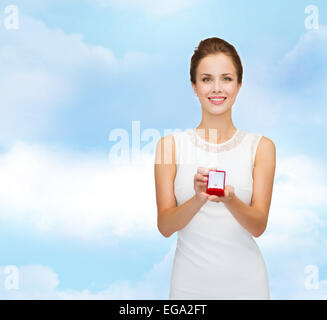 smiling woman holding red gift box with ring - Stock Photo