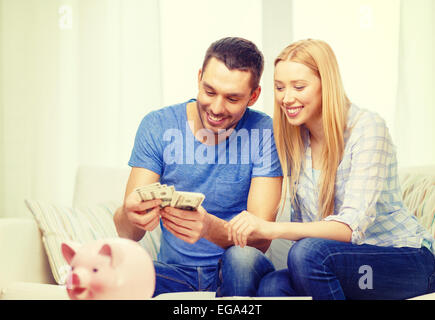 smiling couple counting money at home - Stock Photo