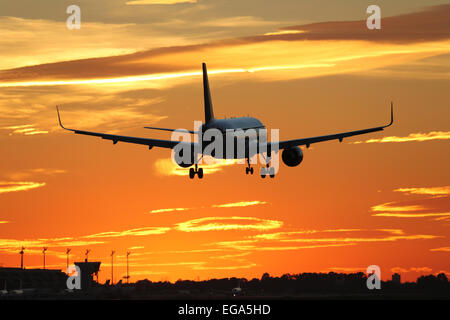 An airplane landing at an airport during sunset on vacation when traveling - Stock Photo
