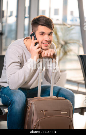 He loves travelling. Portrait of handsome smiling man in casual wear holding his luggage and talking over his mobile - Stock Photo