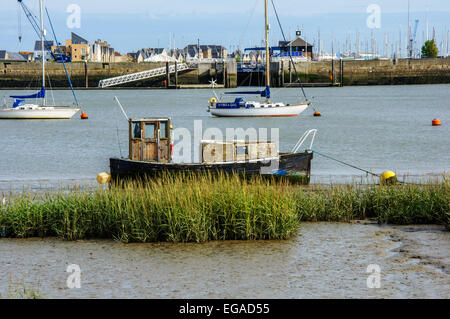 Small boat on The River Medway and Chatham Maritime Marina in background, Upnor, Kent, England, UK - Stock Photo