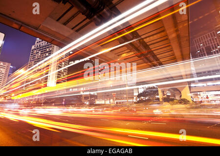 Traffic trails of double decker traveling on a busy road - Stock Photo