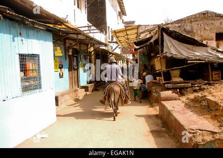 Riding through the streets of Lamu town - Stock Photo