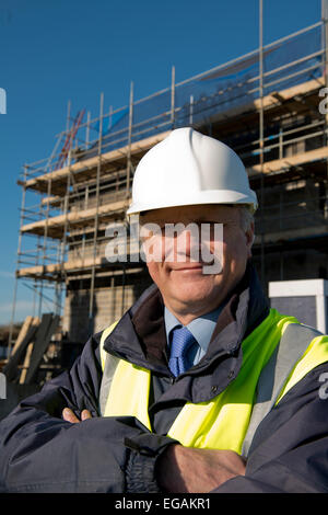 Smiling civil engineer, standing in front of a construction site with his arms folded. - Stock Photo