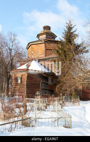 destroyed old Wooden  church on orthodox cemetery in winter, Russia - Stock Photo