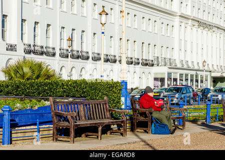 A Man Sits On A Bench Eating Fish and Chips, Eastbourne, Sussex, England - Stock Photo