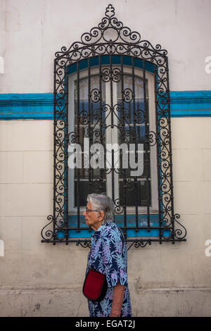 old woman walking past a window of old house with decorative iron grille, Calle San Isidro, Santiago, Chile - Stock Photo