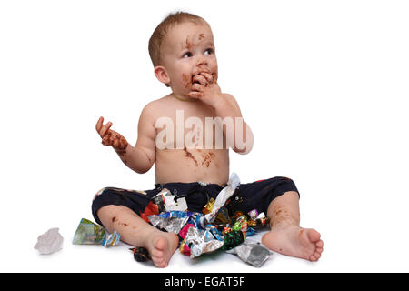 kid eats a lot of chocolate candies - Stock Photo