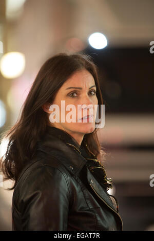 A Woman watches busy rush hour traffice as she prepares to cross Regent's street, central London. - Stock Photo