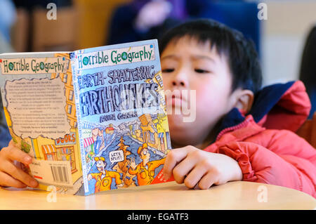 A young Japanese boy reads a book on Earthquakes a few days after the Fukushima disaster - Stock Photo
