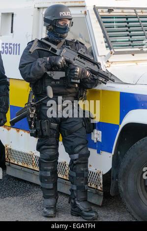 Police officer dressed in ballistic uniform holds a Heckler and Koch G36 machine gun. - Stock Photo