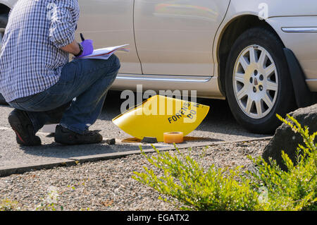 Forensic Officer examines a Stanley knife at a crime scene - Stock Photo