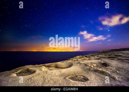 An almost alien and surreal landscape...actually shot on the island of Gozo.  The distant glare and lights are from - Stock Photo