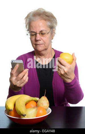 Middle aged woman using an Apple iPhone while eating fruit - Stock Photo