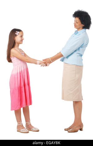 A full length portrait of grandmother holding hands with  her granddaughter. - Stock Photo