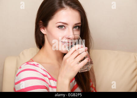 Beautiful young woman drinking water from glass - Stock Photo