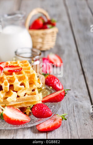 Homemade belgian waffles with ripe strawberry, honey and milk on wooden background - Stock Photo