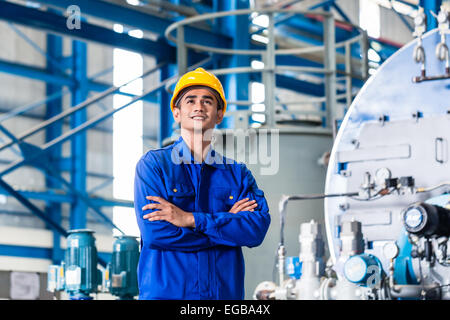 Proud Asian worker standing in production factory - Stock Photo