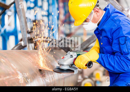 Industrial worker in manufacturing plant grinding to finish a pipeline - Stock Photo