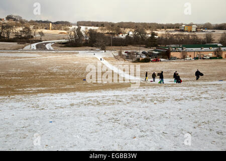 Family with children walking up a hill in the snow for sledding. - Stock Photo