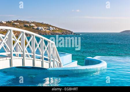 Wooden footbridge over luxury swimming pool, Mykonos, Cyclades, Greece - Stock Photo