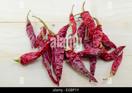 A bunch of dried red peppers on a wooden table - Stock Photo