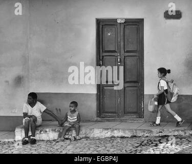 A Cuban woman and young boy sit on a stone step outside a house in Trinidad, Cuba as a young school girl walks by. - Stock Photo