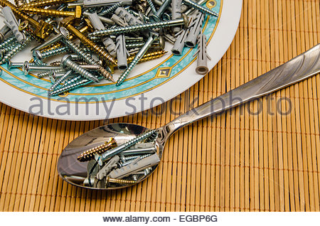Hardware soup made with screws, dowels, and other items. Eat time. Disgusting food. - Stock Photo