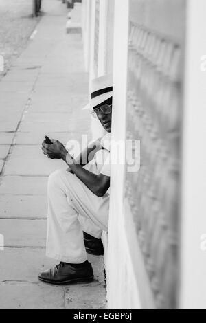 A Cuban man smoking a cigar in a doorway of the Plaza Mayor in Trinidad, Cuba - Stock Photo