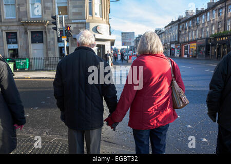 Elderly couple holding hands on the streets of Edinburgh - Stock Photo