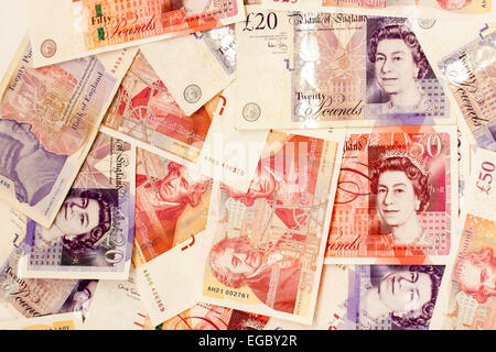 £50 and £20 English banknotes, scattered on floor (unseen), mostly face-up showing Queen's head. - Stock Photo