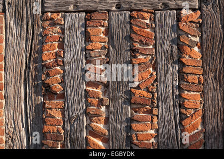 glancing sunlight shows off the finer details of the handmade red clay bricks and wooden oak support timber beams - Stock Photo