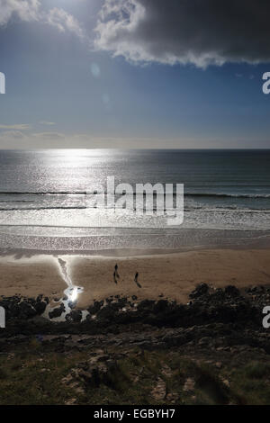 Sun reflecting on sea people playing on beach Caswell Bay Gower South Wales UK - Stock Photo
