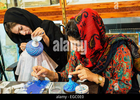 Ahmadi Enamelling, licensed artist of Cultural Heritage Organization, paints cooper vase in her shop, Esfahan, Iran - Stock Photo