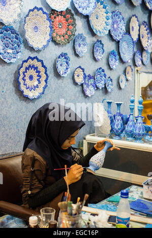 Artist paints cooper vase in Enamel Peykam shop on Emam Khomeini Square in Esfahan, Iran - Stock Photo
