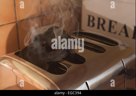 risk of fire smoking burning toast forgotten in the toaster in kitchen catching burning alight glowing red and charred - Stock Photo