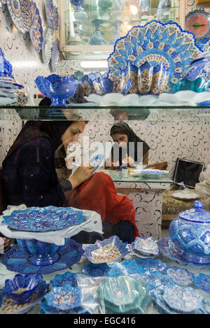 Artists paint cooper plates in Enamel Peykam shop on Emam Khomeini Square in Esfahan, Iran - Stock Photo