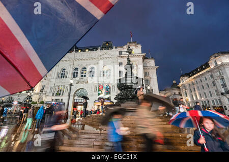 People with Umbrellas at Piccadilly Circus at night, London, UK - Stock Photo