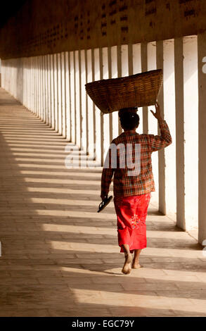 A burmese woman carrying a basket on her head walking, from the rear, Bagan, Myanmar ( Burma ), Asia - Stock Photo