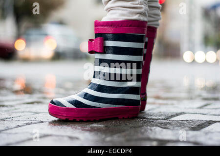 Little girl standing in the rain wearing cute rubber boots - Stock Photo