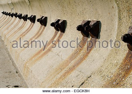 Looking along the sea wall at Aldeburgh in Suffolk with rusting fixing bolts marking the concrete - Stock Photo