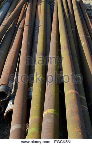 Close-up of a pile of old drill pipes. - Stock Photo