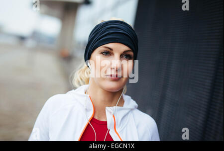 Close-up portrait of attractive and sport woman wearing headband and listening to music on earphones. Fitness female. - Stock Photo